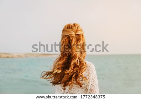 Portrait of a woman curling her eyelashes with the hair wrapped into a towel Stock photo © wavebreak_media