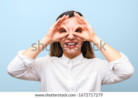 Blue eyed businesswoman holding her glasses against white background Stock photo © wavebreak_media