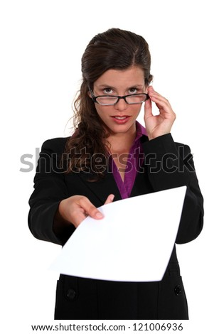 Businesswoman peering over her glasses and holding out a document Stock photo © photography33
