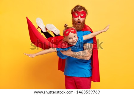 Father and daughter pretending to be superhero against trees amidst buildings in city Stock photo © wavebreak_media