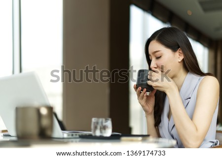 a young girl is sitting at a table in the office holding a red cup in her hand and taking a sheet w stock photo © traimak