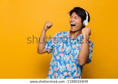 Excited young asian man standing isolated over yellow background play games by mobile phone. Stock photo © deandrobot