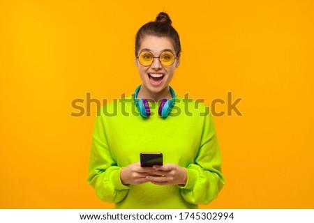 Portrait of shocked woman 20s wearing sweatshirt holding smartph Stock photo © deandrobot