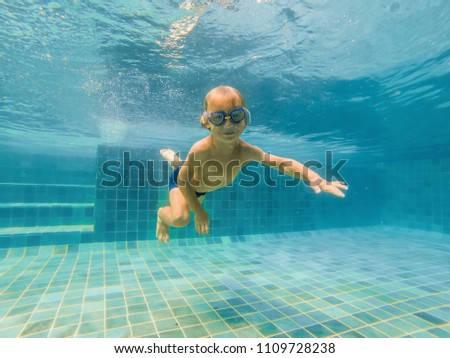 A child boy is swimming underwater in the see, smiling and holding breath, with swimming glasses stock photo © galitskaya