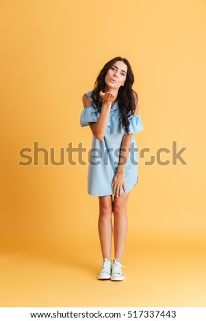Beautiful charming brunette sending air-kiss Isolated on gray background stock photo © studiolucky