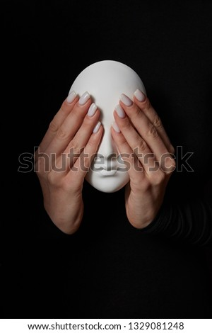Woman's fingers close eyes of gypsum mask face on a black background. See no evil. Concept three wis Stock photo © artjazz