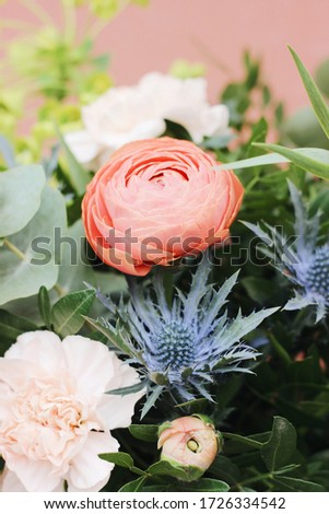 Fresh flowers living coral roses and eryngium as a congratulate bouquet in girl's hand with tattoo,  Stock photo © artjazz