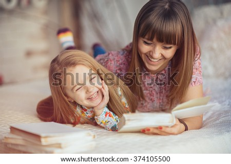 Portrait of a mother and daughter reading a book lying and relax in the bed foto stock © Lopolo