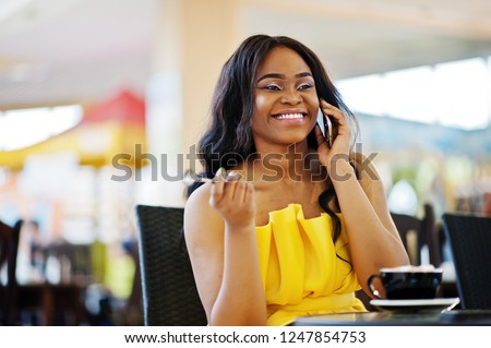 Stylish american woman at yellow dreess posed at cafe with cup of cappuccino at hands. Stock photo © ElenaBatkova