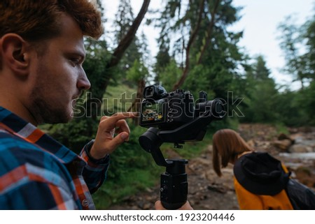 the production team on a commercial video shoot. Steadicam operator uses the 3-axis camera stabilize Stock photo © galitskaya