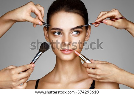 Beautiful girl surrounded by hands of makeup artists with brushes and lipstick near her face. Photo  Stock photo © serdechny
