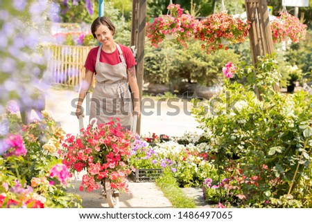 happy young garden worker in apron pushing cart with new sorts of flowers stock photo © pressmaster