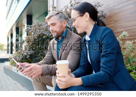 Young woman with drink looking at display of touchpad held by colleague Stock photo © pressmaster