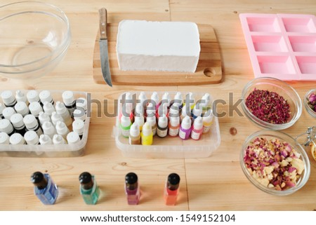 Bar of white hard soap mass, essential oils and dry floral petals in bowls Stock photo © pressmaster