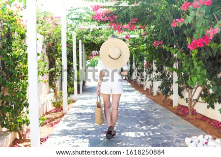 Blond girl in straw hat in front of pink bougainvillea flowers Stock photo © dashapetrenko