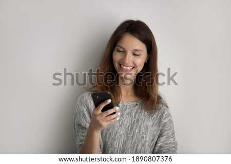 Smiling red haired female focused in modern cellular, happy to recieve text message, poses at workpl Stock photo © vkstudio