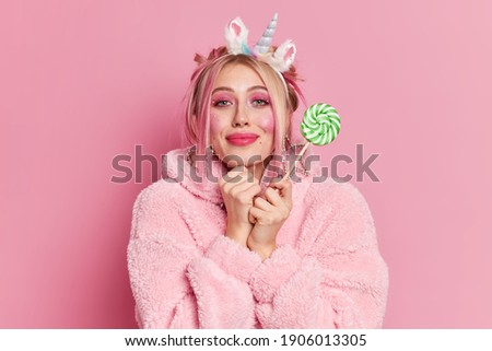 Adorable young European woman looks positively at camera, keeps hands together under chin, wears str Stock photo © vkstudio