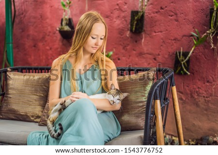 Young woman having a mediterranean breakfast seated at her sofa and with her cat and eats Healthy tr Stock photo © galitskaya
