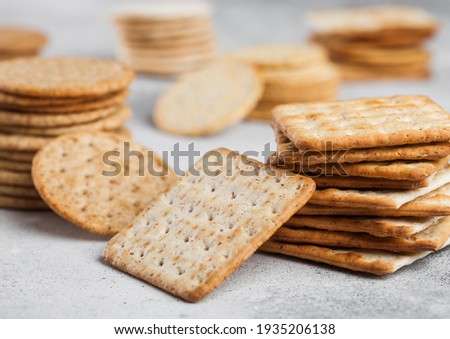 Stack of various organic crispy wheat flatbread crackers with sesame and salt on light kitchen table Stock photo © DenisMArt