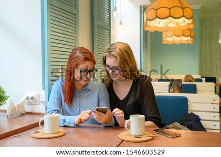 Photo of cheerful woman using cellphone and drinking coffee takeaway Stock photo © deandrobot