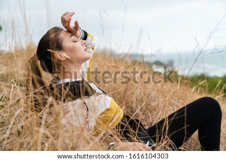 Photo of tired beautiful woman using earpods while resting Stock photo © deandrobot