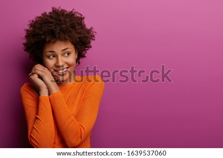 Happy pretty african woman isolated over violet background holding orange. Stock photo © deandrobot