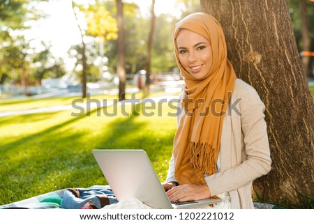 Photo of young islamic girls wearing headscarfs, sitting on benc Stock photo © deandrobot