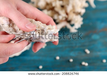 Hand with tweezers holding pearl and oyster on wooden background Stock photo © galitskaya