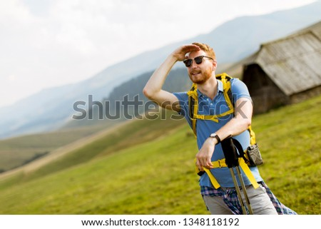 Handsome young red hair man with sunglasses hiking on the mounta Stock photo © boggy