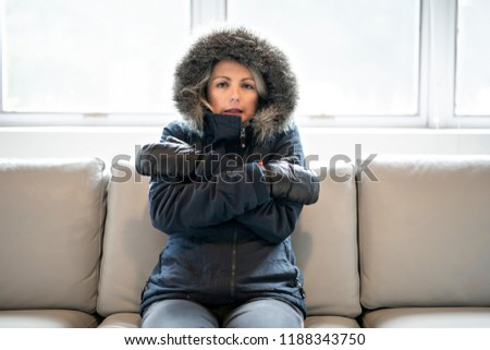 Woman have cold on the sofa at home with winter coat Stock photo © Lopolo