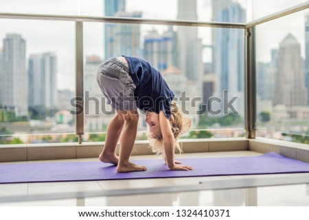 Happy little boy is practicing yoga on his balcony with a panoramic view of the big city Foto stock © galitskaya
