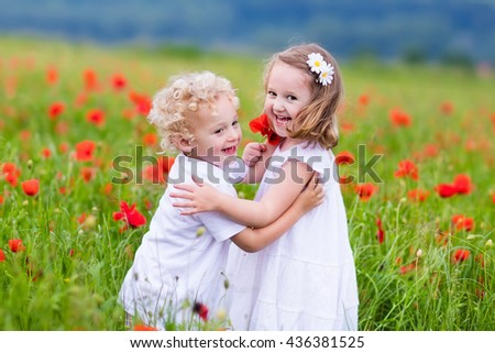 little curly blond boy and girl play in poppy flower field child picking red poppies toddler kid i stock photo © elenabatkova
