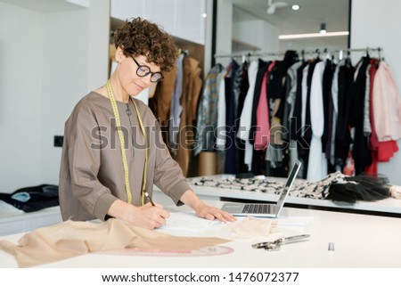 Pretty young female tailor making sketch of new clothes on paper Stock photo © pressmaster