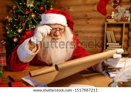 Santa in eyeglasses reading attentively big letter of Christmas wishes Stock photo © pressmaster