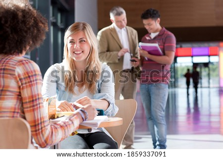 Stock photo: Side view of young school teacher helping girl with study while kneeling in front of his desk in cla