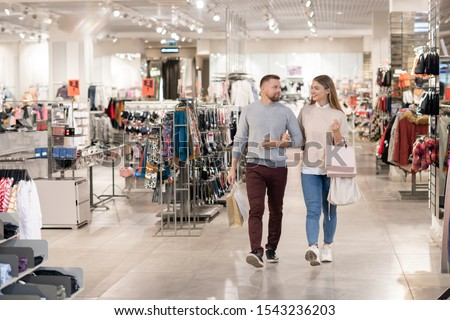 Happy young dates carrying paperbags while moving along clothing department Stock photo © pressmaster