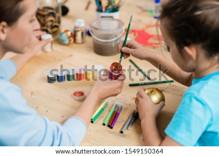 Creative schoolgirl with paintbrush taking some paint from small plastic jar Stock photo © pressmaster