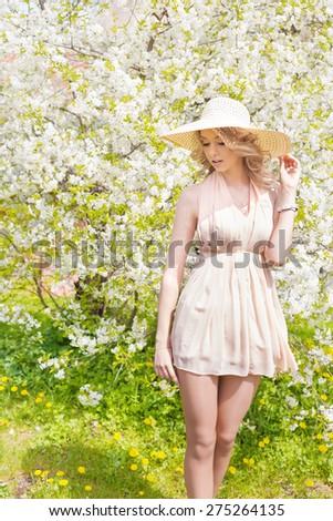 Cute girl wearing hat and white dress stand in the pink flower field of Sunn Hemp Crotalaria Juncea Stock photo © ElenaBatkova