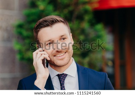 Headshot of handsome unshaven young male has conversation with service operator, has happy expressio Stock photo © vkstudio