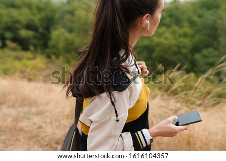 Photo of nice brunette woman using earpods while working with bag Stock photo © deandrobot