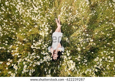 Happy young dreamy beautiful woman lying on the grass with red flower. Sunny day. Stock photo © deandrobot