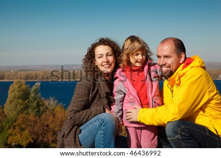 Little girl with mum and daddy, in bright autumn day. Happy family on nature. Stock photo © Paha_L