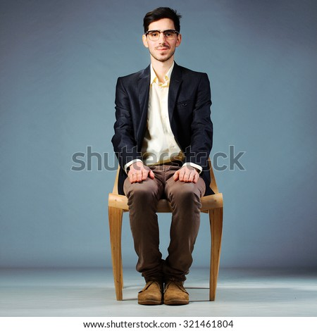 confident businessman sitting on wooden chair with hands folded Stock photo © feedough