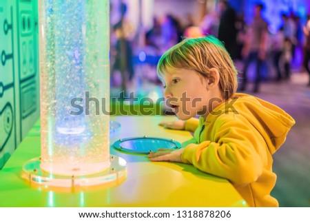 Smart boy scientist making physical experiments in the laborator Stock photo © galitskaya