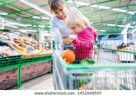 Mother having her toddler riding in shopping cart of supermarket Stock photo © Kzenon