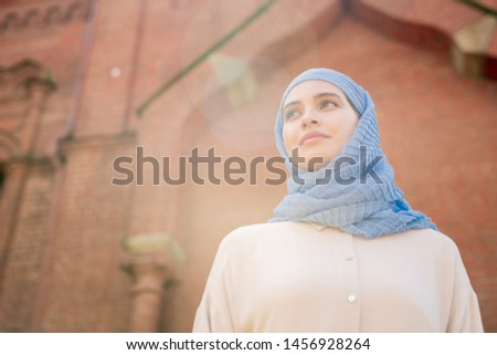 Young female in hijab looking forwards while taking walk down ancient city Stock photo © pressmaster