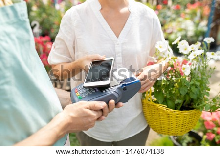 Garden center client using contactless payment app to pay for fresh flowers Stock photo © pressmaster