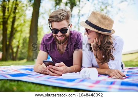 Couple using mobile phone while lying on picnic blanket in the park Stock photo © wavebreak_media