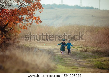 Boy and girl brother and sister running on the steppe road on the background of high yellow grass Stock photo © ElenaBatkova