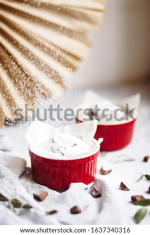 Chocolate muffins in red cups. Small glazed ceramic ramekin with brown cakes on a gray and white bac Stock photo © user_15523892